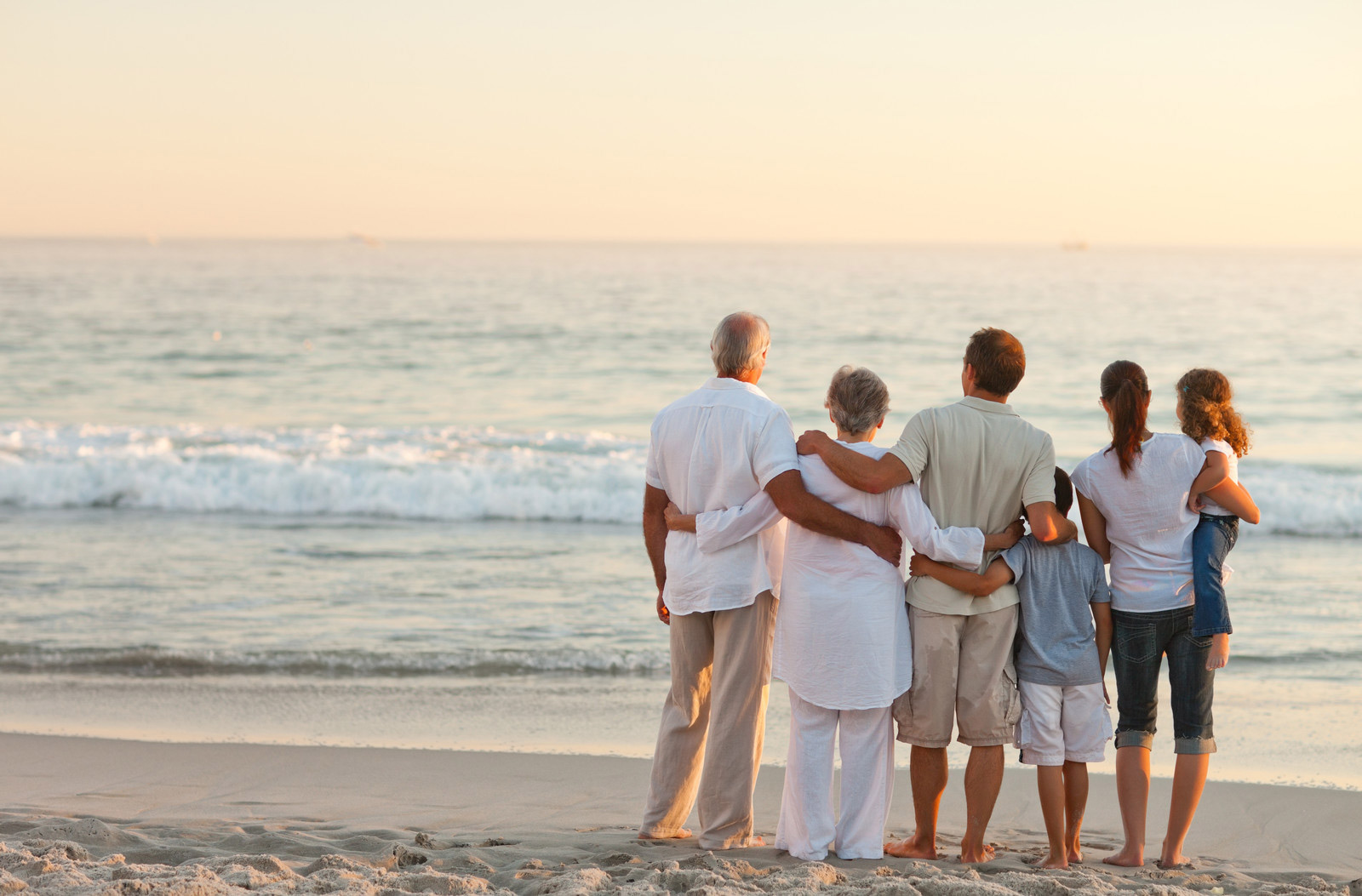 multigenerational family standing on the beach looking out at ocean